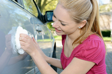Frau poliert Auto-Lack mit Politur