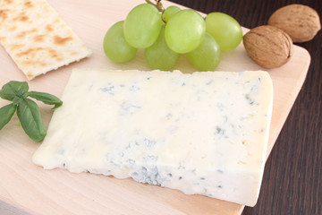 Gorgonzola blue cheese with grapes  on wooden chopping board
