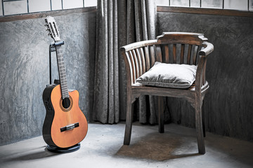 acoustic guitar and wooden armchair