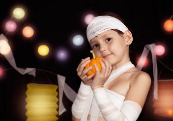 child wearing mummy costume holding halloween pumpkin