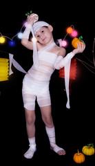 child dressed as mummy holding halloween pumpkins