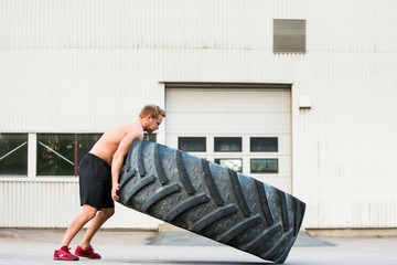 Male Athlete Flipping Large Tire