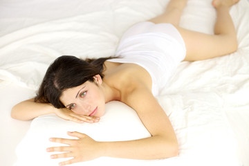 Beautiful woman laying in bed thinking