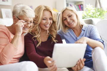 Loving family of women using digital tablet