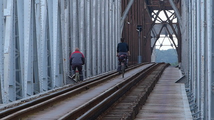 Dangerous bicycle riding on the track at the railway bridge