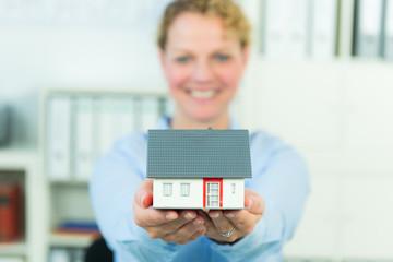 geschäftsfrau hält miniaturhaus in den händen