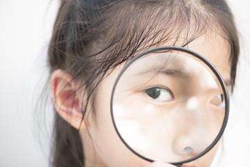 Little Asian girl looking through magnifier.