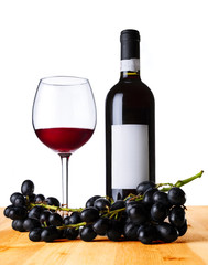 Red wine in the glass and bottle with grape on wood table.