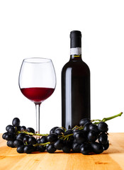 Red wine in glass and bottle with grapes on wood table.