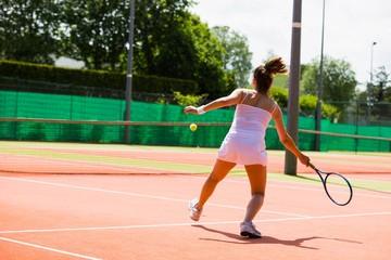 Pretty tennis player hitting ball