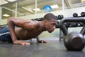Shirtless muscular man doing push ups in gym