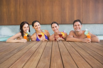 Cheerful people with drinks in swimming pool