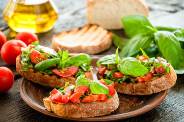 Italian bruschetta with chopped vegetables, herbs and oil on gr
