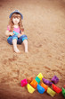 child playing with paper boats on sand