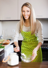 Happy woman with  flour in home kitchen
