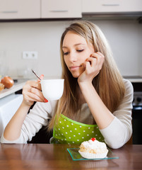 woman drinking tea with cake   in  kitchen