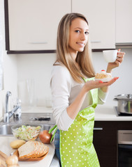 Housewife in apron drinking tea with cake