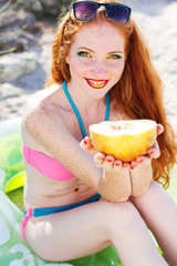 Smiling girl with freckles holding melon