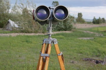 A binoculars with a tripod with a azimuth head in a forest