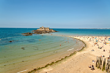 Beach of Saint Malo with fortress and tourists. Blue sky. Britta