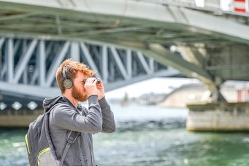 bearded young man with backpack headphone and binocular