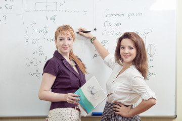Cheerful teacher with students posing in front of blackboard