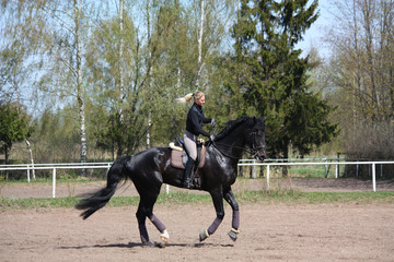 Young woman riding black horse
