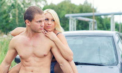Sexy young couple siting on the car's hood.