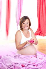 Hübsche Schwangere im Schlafzimmer mit Rosenblättern