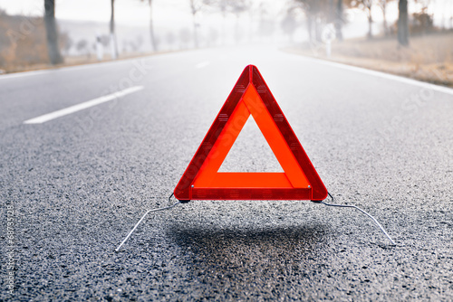 canvas print picture Bad Weather Driving - Warning Triangle on a Misty Road