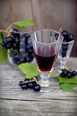 berries and blackcurrant leaves with drink of black currant