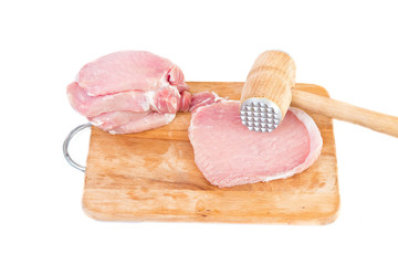 raw meat and meat tenderizer on board