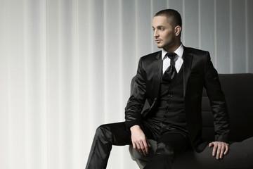 elegant young fashion man in tuxedo  sitting on a sofa