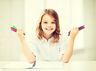 smiling girl showing colorful felt-tip pens
