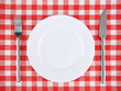 Plate with fork and knife on a red checkered tablecloth. - 68736764