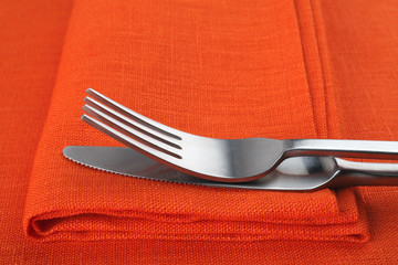 Fork and knife on orange napkin and tablecloth.
