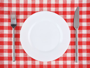 Plate with fork and knife on a red checkered tablecloth.