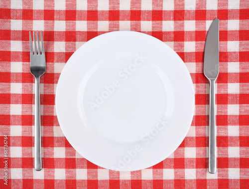 Foto Spatwand Boord Plate with fork and knife on a red checkered tablecloth.
