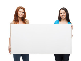 two smiling young girls with blank white board