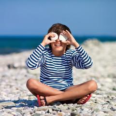 Мальчик с камнями в руках на берегу моря