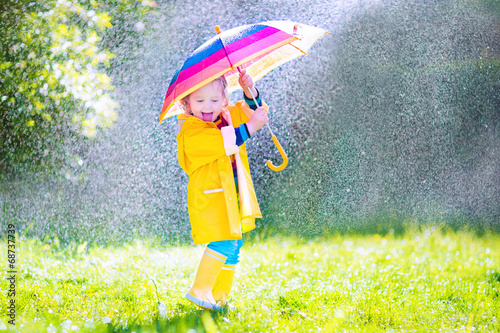 canvas print picture Funny little toddler with umbrella playing in the rain