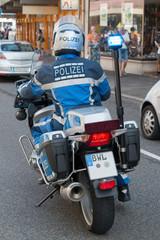 Polizist in blauer Uniform auf Mottorrad, Ansicht von hinten