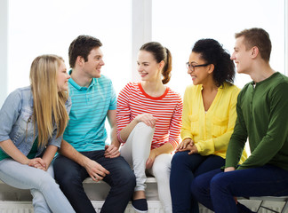 five smiling teenagers having fun at home