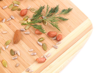 Various nuts and herb on cutting board.
