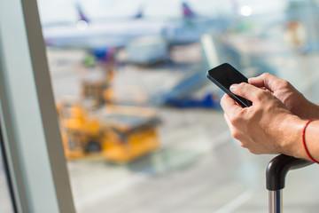Close up man's hands using cellphone inside airport