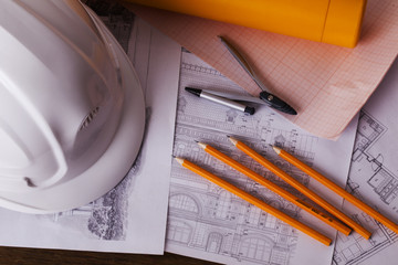 white helmet and blueprints pencils