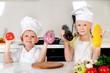 Two smiling children holding up fresh vegetables
