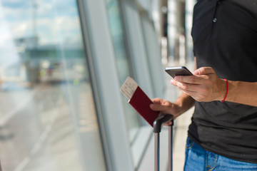 Man holding cell phone, passports and boarding passport at