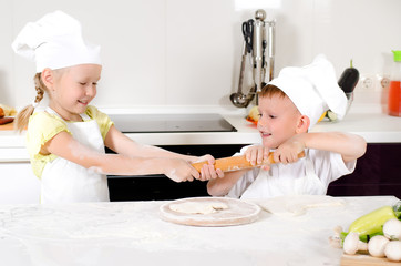 Two young children fighting over a rolling pin
