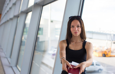 Woman holding passports and boarding pass at airport waiting the